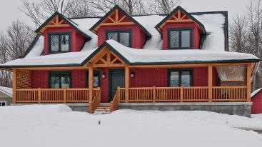 hybrid home with 3 dormer and covered porch in winter